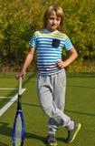 Muchacho que se coloca con la estafa y la bola de tenis en la corte Imagenes de archivo