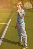 Muchacho que se coloca con la estafa y la bola de tenis en la corte Fotos de archivo libres de regalías