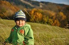 Muchacho que se coloca en bent-grass Fotos de archivo libres de regalías