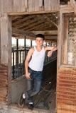 Muchacho que se coloca en el granero viejo Fotografía de archivo