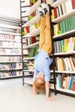 Muchacho que se coloca en inclinarse al revés de los brazos en el estante Imagenes de archivo