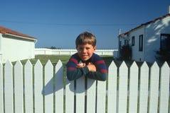 Muchacho que se coloca en la cerca de piquete blanca Imagen de archivo