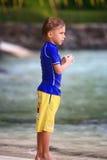 Muchacho que se coloca en la playa Foto de archivo