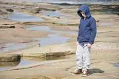 Muchacho que se coloca en rocas Imagen de archivo libre de regalías
