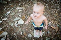 Muchacho que se coloca en una roca Imagenes de archivo