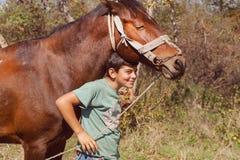 Muchacho que se divierte con el caballo en la granja del pueblo Fotografía de archivo