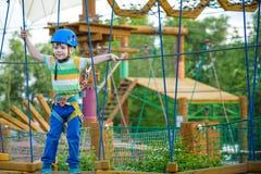Muchacho que se divierte en el parque de la aventura niño que sube en un pla de la cuerda Fotos de archivo libres de regalías