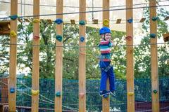 Muchacho que se divierte en el parque de la aventura niño que sube en un pla de la cuerda Imágenes de archivo libres de regalías