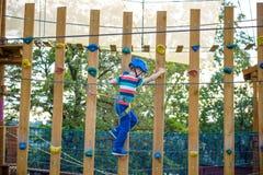 Muchacho que se divierte en el parque de la aventura niño que sube en un pla de la cuerda Imagen de archivo