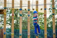 Muchacho que se divierte en el parque de la aventura niño que sube en un pla de la cuerda Imagenes de archivo