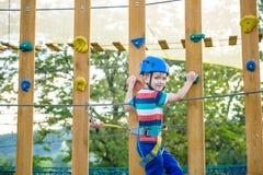 Muchacho que se divierte en el parque de la aventura niño que sube en un pla de la cuerda Imagen de archivo libre de regalías