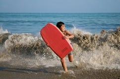 Muchacho que se ejecuta con la tarjeta que practica surf Foto de archivo libre de regalías