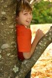Muchacho que se inclina contra un árbol Imágenes de archivo libres de regalías