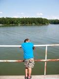 Muchacho que se inclina en cercar con barandilla por el lago Imágenes de archivo libres de regalías