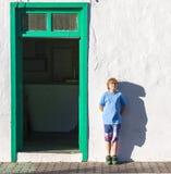 Muchacho que se inclina en una pared y que lanza una sombra divertida Imagen de archivo libre de regalías