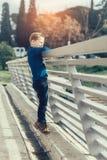 Muchacho que se inclina sobre una verja del puente que mira abajo el río Fotografía de archivo libre de regalías