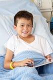 Muchacho que se relaja en cama de hospital con la tablilla de Digitaces Fotos de archivo