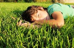 Muchacho que se relaja en hierba Foto de archivo