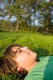 Muchacho que se relaja en hierba Fotos de archivo