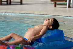 Muchacho que se relaja en una piscina Imagen de archivo libre de regalías