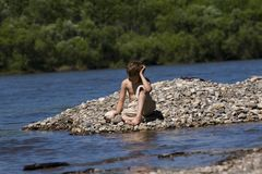 Muchacho que se relaja por el lago Imagen de archivo