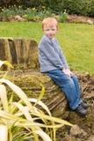 Muchacho que se sienta afuera Fotografía de archivo libre de regalías