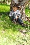 Muchacho que se sienta bajo un árbol de goma Imagen de archivo