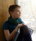 Muchacho que se sienta cerca de ventana con el libro y que mira el día de invierno Foto de archivo