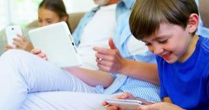 Muchacho que se sienta con la familia usando el teléfono móvil almacen de metraje de vídeo