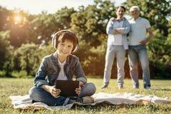 Muchacho que se sienta con su tableta y auriculares Imágenes de archivo libres de regalías