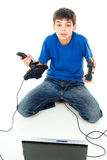 Muchacho que se sienta con un ordenador y una palanca de mando Imagen de archivo