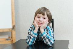 Muchacho que se sienta en casa y mirada Imagen de archivo