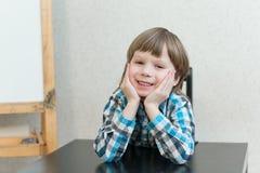 Muchacho que se sienta en casa y mirada Foto de archivo libre de regalías