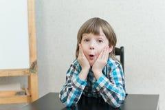 Muchacho que se sienta en casa y mirada Imágenes de archivo libres de regalías