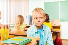 Muchacho que se sienta en clase de escuela y que parece derecho Fotos de archivo