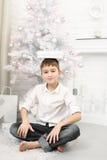 Muchacho que se sienta en el árbol de navidad con los regalos alrededor Imagenes de archivo