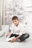 Muchacho que se sienta en el árbol de navidad con los regalos alrededor Imagen de archivo