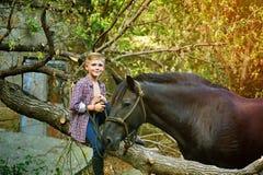 Muchacho que se sienta en el árbol viejo que presenta con un caballo después de un entrenamiento Foco en el muchacho Foto de archivo