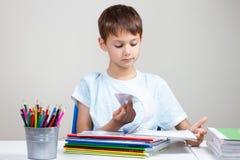 Muchacho que se sienta en el escritorio con la pila de libros y de cuadernos de escuela y que hace la preparación en casa Fotos de archivo