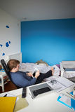 Muchacho que se sienta en el escritorio en dormitorio usando la tableta de Digitaces Foto de archivo libre de regalías