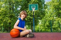Muchacho que se sienta en el patio con la bola Fotografía de archivo