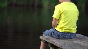 Muchacho que se sienta en el puente en la piscina almacen de metraje de vídeo
