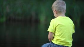Muchacho que se sienta en el puente en la piscina metrajes