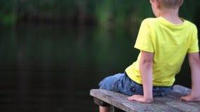 Muchacho que se sienta en el puente en la piscina almacen de video