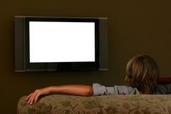 Muchacho que se sienta en el sofá que mira la televisión con pantalla grande Imagenes de archivo