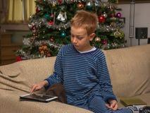 Muchacho que se sienta en el sofá usando una tableta para la letra para el papá de la Navidad, árbol de navidad en el fondo Imágenes de archivo libres de regalías