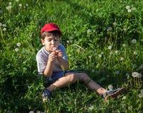 Muchacho que se sienta en hierba y que sopla un diente de león Foto de archivo libre de regalías