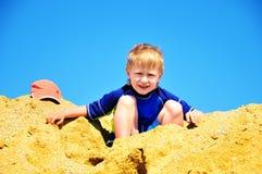 Muchacho que se sienta en la arena enorme de la pila Foto de archivo libre de regalías