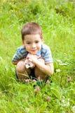 Muchacho que se sienta en la hierba en el parque Imagenes de archivo