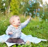 Muchacho que se sienta en la hierba que juega con las burbujas de jabón imagenes de archivo